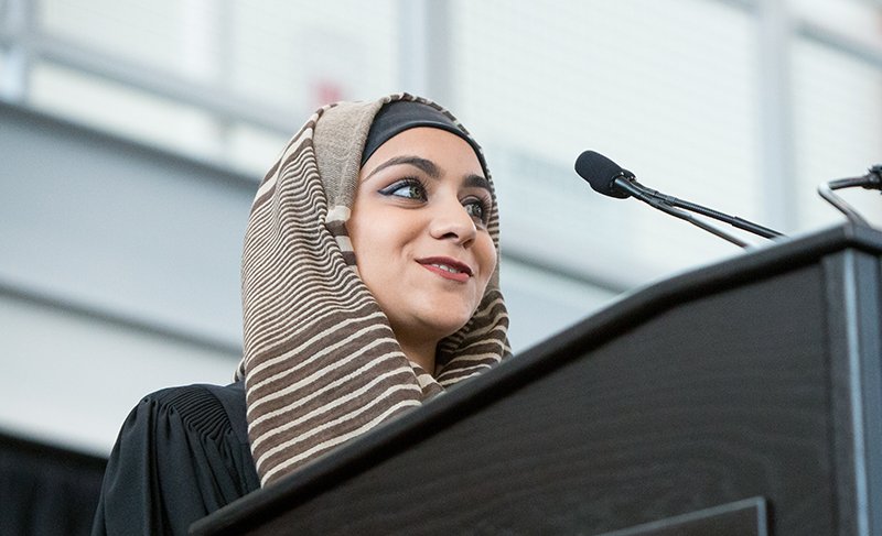 Female student smiles in front of podium and microphone