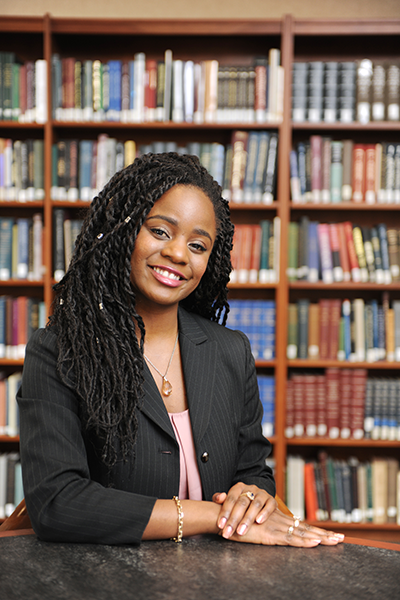 TaLona Holbert poses in front of law books